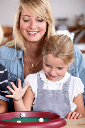 Mother and daughter playing dice Stock Photo - 14230119