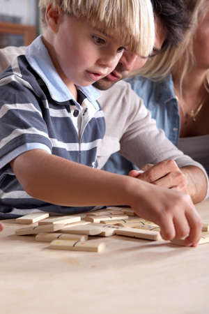 Young boy playing dominoes with his father Stock Photo - 14213225