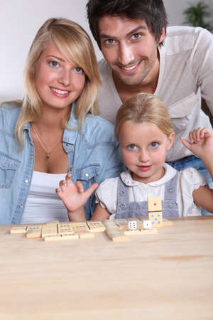 Parents and daughter playing dominoes photo