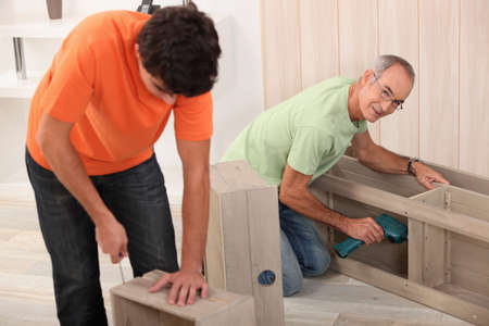 Father and son putting together flat pack furniture photo