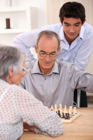 Young man watching an older couple play chess photo