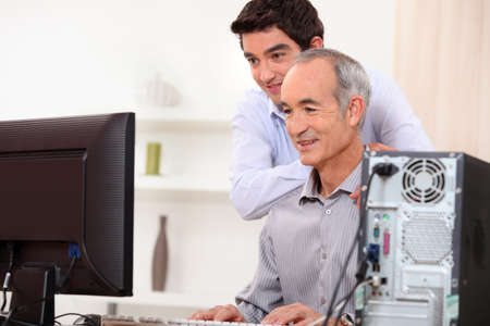 Young man teaching an elderly man computer skills photo