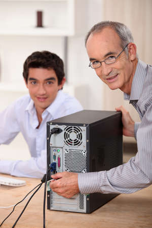 old pc: Happy technician fixing a computer Stock Photo