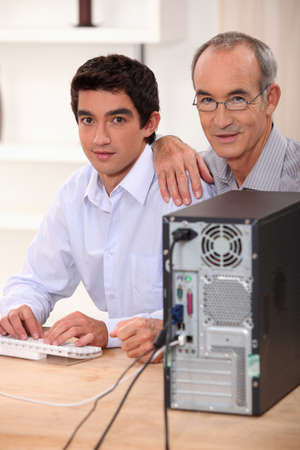 plugging: Grandfather and grandson with computer Stock Photo