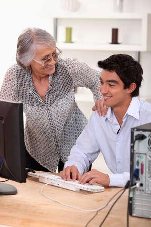 Young man using computer and happy senior woman photo