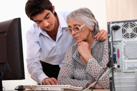 Young man showing elderly lady how to use computer photo
