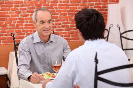 amigas conversando: Anciano con su nieto para una comida Foto de archivo