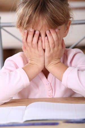 difficulties: Frustrated girl unable to complete her homework Stock Photo