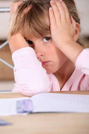 Girl tired of doing homework photo