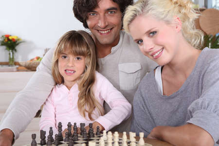 pawn adult: Family playing chess together Stock Photo