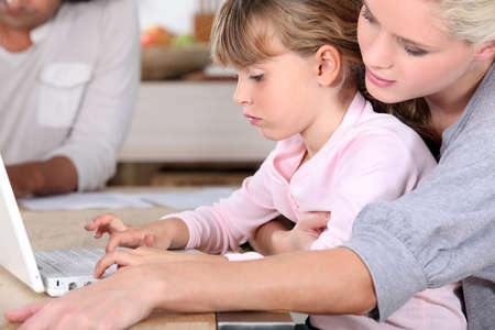 young mother teaching her daughter how to use computer photo