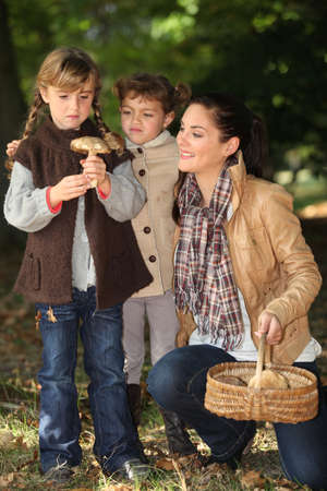 collects: Mother and daughters picking mushrooms Stock Photo