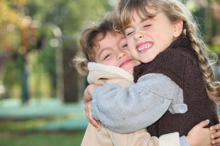 best friends girls: Young girls hugging outside