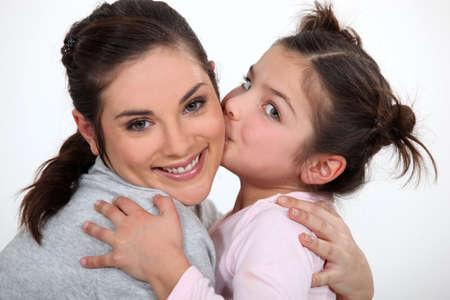 vejez feliz: niña besa a su madre