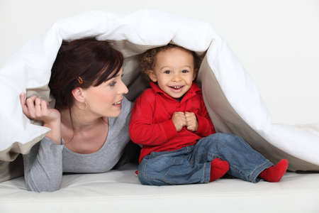 counterpane: Mother and son hiding under blanket Stock Photo