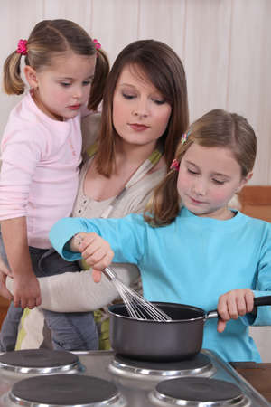 Young woman and little girls preparing a cake photo