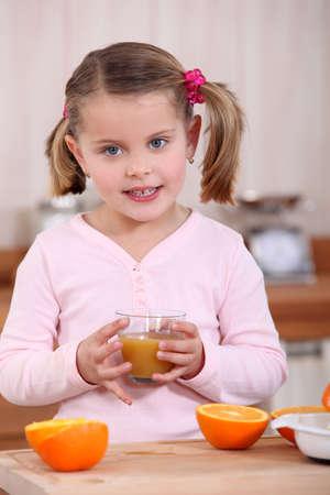 Girl drinking orange juice photo