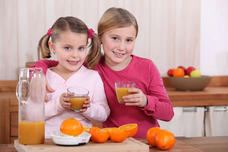 Two sisters drinking orange juice in kitchen Stock Photo - 14213551