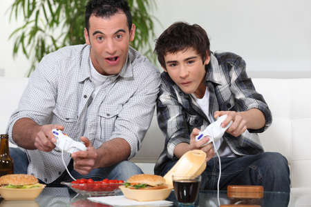computer games: Father and son playing computer games and eating junk food Stock Photo