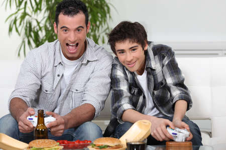 accomplices: father and son playing to video games Stock Photo