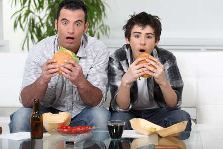 gratified: Father and son sat on the sofa eating burgers