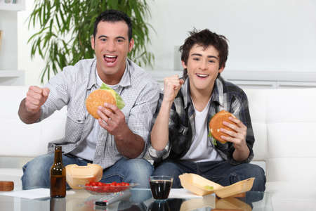 people watching tv: Padre e hijo comiendo hamburguesas en la parte frontal de la TV