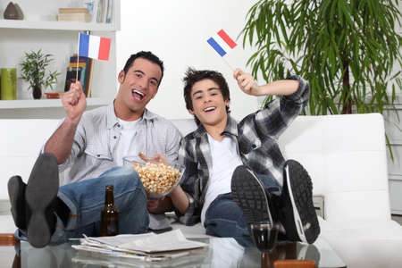cheering fans: two guys watching football on the couch