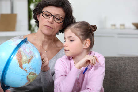 Grandmother with granddaughter looking at globe photo