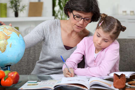 Mother teaching daughter from home photo