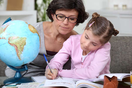 Woman helping a child with her geography homework photo