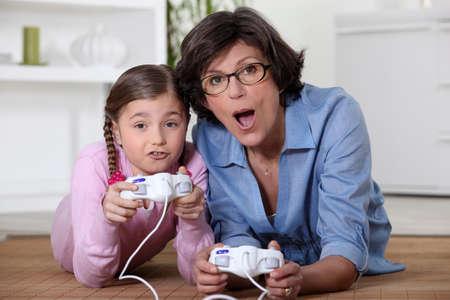 jugando videojuegos: Madre jugando vide-juegos con la hija Foto de archivo