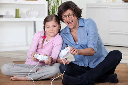 Girl and her grandmother playing computer games photo