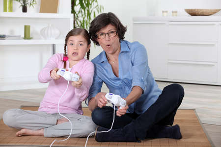 A mother and her daughter playing video game. photo