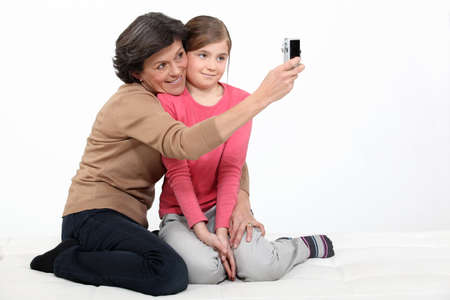 Woman taking a picture of herself with her granddaughter photo