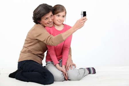 Mujer que toma una foto de ella con su nieta