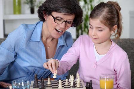 jugando ajedrez: Madre e hija jugando al ajedrez