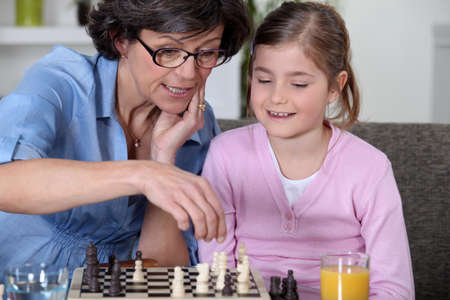 A mother and her daughter playing chess. photo