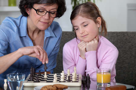 Mother and daughter playing chess photo