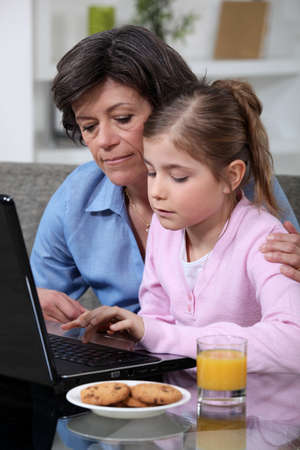 Child and her grandmother using a laptop photo