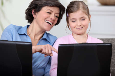 Mother and daughter having fun with their laptops photo