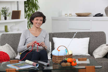 woman sitting on settee knitting photo
