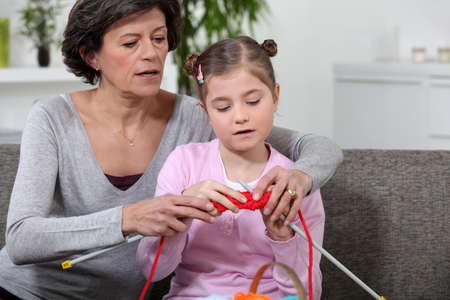 grandmother teaching granddaughter how to knit photo