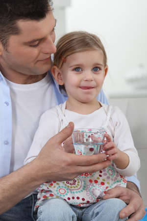 hairclip: Man with little girl drinking glass of water
