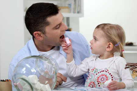 Father and daughter eating sweets photo