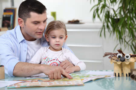 father teaching daughter: Father and daughter reading together Stock Photo