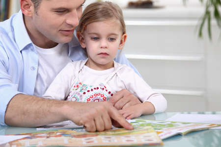 father teaching daughter: Father and daughter with a magazine