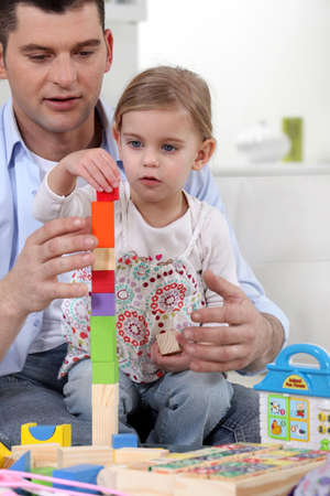 Father helping daughter to build towel from wooden blocks photo