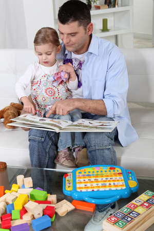 Father and daughter at home reading a book photo