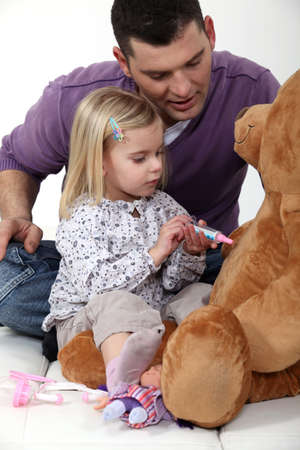 Man with little girl playing with teddy bear photo