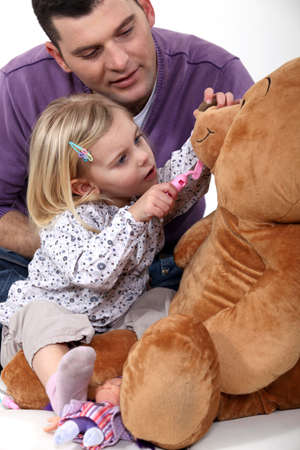 Father and daughter playing dentist with a teddy bear photo